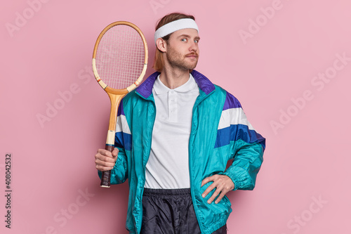 Obraz Active self confident sportsman holds tennis racket braggs about his winning of competition dressed in activewear enjoys game isolated over pink background. People and healthy lifestyle concept - fototapety do salonu