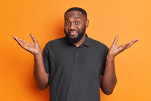 Dark Skinned Clueless Man With Beard Spreads Palms Shrugs Shoulders Looks Unaware Faces Difficult Choice Dressed In Casual Black T Shirt Isolated Over Vivid Orange Background. Human Perception