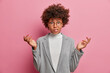 Photo of puzzled young African American woman entrepreneur with curly hair raises hands shrugs shoulders looks clueless or nervous says so what dressed in grey clothes poses against pink background