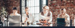 canvas print picture - Office business team concept. Four teammates sitting in a line and working at big black table. Wide screen orientation