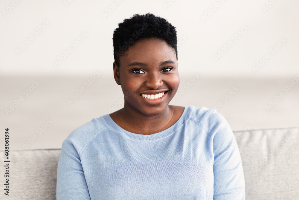 Fototapeta Portrait of casual young black woman smiling confidently