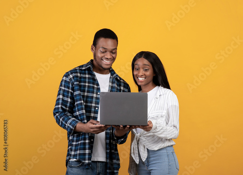Obraz na plátně Happy millennial african american couple looking at laptop and choosing purchase