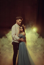 Fantasy Couple Hugging In Dark Room Full White Smoke. Image Of Lovers King And Queen. Medieval Male Prince In Golden Crown, Vintage Costume Clothing. Girl Princess In Long Glamorous Blue Dress Gown