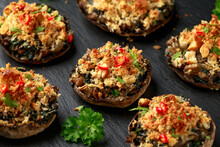 Stuffed Mushrooms With Spinach, Bread Crumbs And Cheese On Stone Board