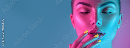 Obraz High Fashion model girl in colorful bright UV lights posing in studio, portrait of beautiful woman with trendy make-up and manicure. Art design, colorful make up. Over colourful background - fototapety do salonu