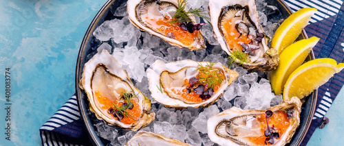 Fotografie, Obraz Oysters platter with lemon caviar and ice served on a Blue marine table