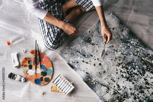 Tela young handsome man paints abstract picture with oil paints at home isolated