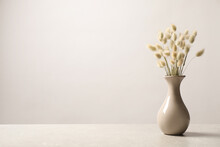 Dried Flowers In Vase On Table Against Light Background. Space For Text