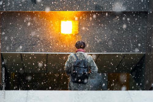 Woman descends into an underground passage during a winter blizzard Fototapet