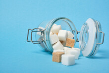 Cubes Of Brown And White Sugar In A Jar On A Blue Background