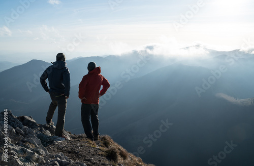 Obraz Two men standing standing with trekking poles on cliff edge and looking at sunset rays over the clouds. Successful summit concept image. - fototapety do salonu