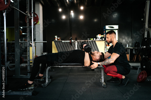 Canvas Print personal trainer helping and assisting man in the gym
