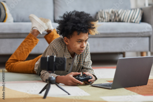 Obraz Full length portrait of teenage African-American boy playing videogames while lying on floor at home with camera filming for online streaming, copy space - fototapety do salonu
