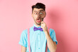 Leinwandbild Motiv Funny man in bow-tie look through magnifying glass, squinting and making silly faces, standing on pink background