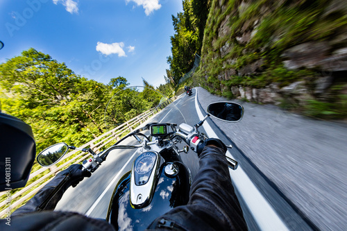 Obraz POV of motorbiker holding steering bar, riding in Alps in beautiful dramatic sky. Travel and freedom, outdoor activities - fototapety do salonu