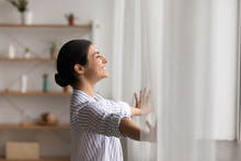 Bathing In Sunlight. Excited Young Indian Lady Meet First Morning At New Flat House Part Curtains Enjoy Being Homeowner. Happy Hindu Female Open Drapes On Window Breath Fresh Air Close Eyes In Delight