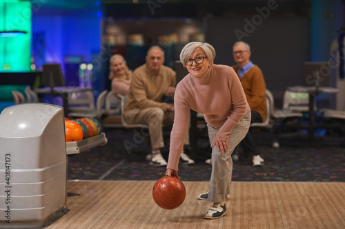 Foto Full length portrait of joyful senior woman playing bowling with group of friend