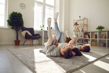 Happy Family Spending Leisure Time At Home. Carefree, Cheerful Young Mother And Children Lying On Warm Floor Rug In Their Apartment. Mum And Kids Relaxing On Soft Carpet In Cosy Sunny Living Room