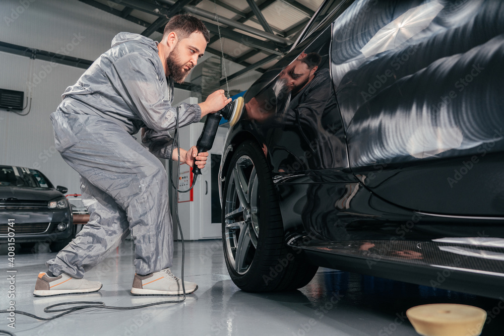 Fototapeta Worker polishing car with special grinder and wax from scratches at the car service station. Professional car detailing and maintenance concept