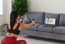 Young Fit Female Athlete In Sportswear Doing Workout With Dumbbels Repeating After Coach During Online Training From Home. Active Healthy Lifestyle, Training At Home And Online Training Concept