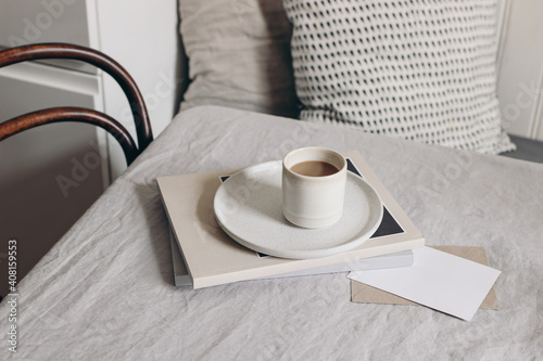 Breakfast still life scene. Cup of coffee, magazine and greeting card mockup on beige linen tablecloth. Scandinavian interior design. Blurred dining room background with old chair and table. © tabitazn