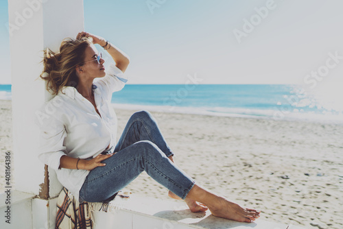 Fotografía Thoughtful attractive woman dressed in stylish casual clothes enjoying good sunny weather on a sunny beach