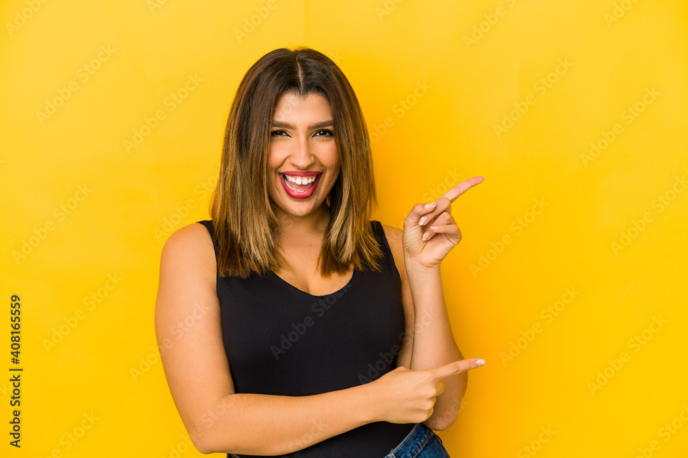 Fototapeta Young indian woman isolated on yellow background pointing with forefingers to a copy space, expressing excitement and desire.