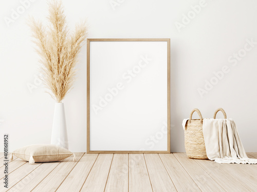 Vertical frame mockup standing on wooden floor in living room interior with dried pampas grass, woven basket, blanket and pillow with tassels on white wall background Fototapete