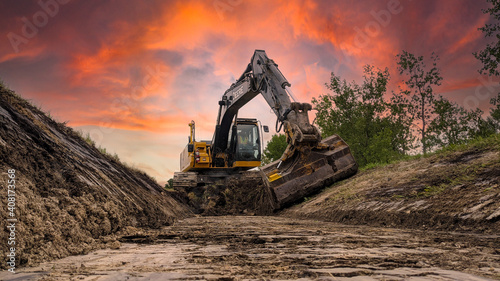 Fototapeta John Deere 210g excavator with a tilt bucket digging a new ditch along the side of the road. obraz