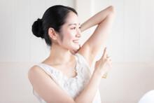 制汗スプレー・香水を使う女性