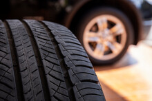 Close Up Of Old Tire With Car Wheel Background. Tire Workshop And Change Old Wheel On The Car. Used Car Tires Stacked In Piles At Tire Fitting Service Repair Shop