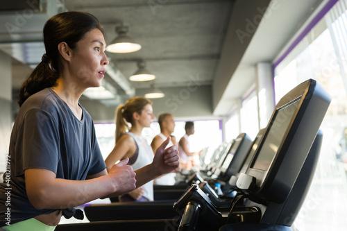 Athletic girls running on treadmill in fitness club Wallpaper Mural