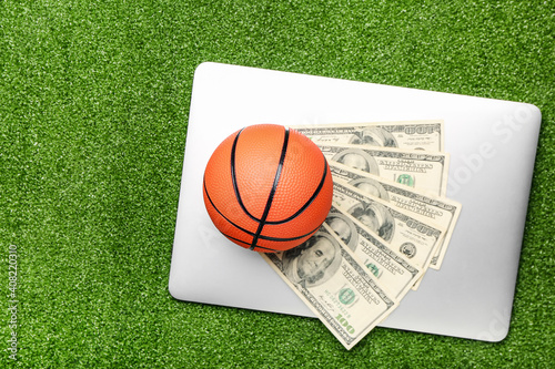 Photo Money, laptop and ball for playing basketball on color background