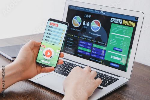 Foto Man placing sports bet at home