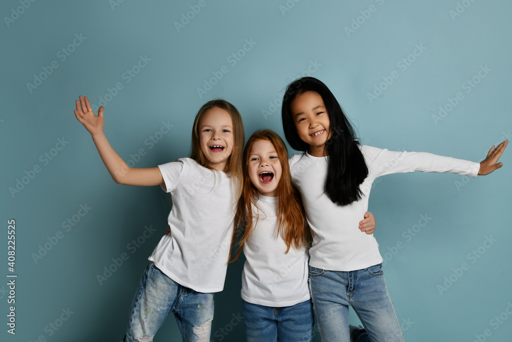 Fototapeta Cheerful multiracial girls friends in jeans and white t-shirts and longsleeves shirt have fun together laughing playing hugging each other over blue background. Happy childhood, stylish look