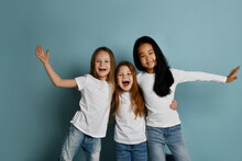 Cheerful Multiracial Girls Friends In Jeans And White T-shirts And Longsleeves Shirt Have Fun Together Laughing Playing Hugging Each Other Over Blue Background. Happy Childhood, Stylish Look