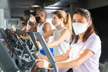 Slim Athletic People In Protective Masks Running On Treadmill In A Fitness Club