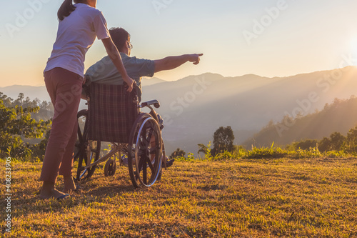 Carta da parati Rear view of disabled handicapped man in wheelchair and care helper walking on mountain at sunset