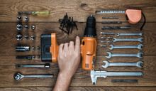 Hand Holding Cordless Screwdriver, Wrenches And Tool Kit On An Old Wooden Table