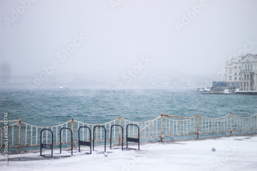 Fotografie, Obraz Snow storm on the seaside boulevard. Snow by the sea.