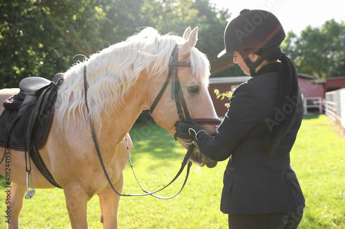 Fotografie, Tablou Young woman in horse riding suit and her beautiful pet outdoors on sunny day