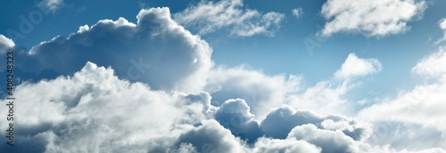 Fototapeta Clear blue sky with glowing white cumulus clouds. Midday sun. Panoramic dramatic cloudscape. Concept art, meteorology, climate change, religion, heaven, hope, peace, graphic resources obraz