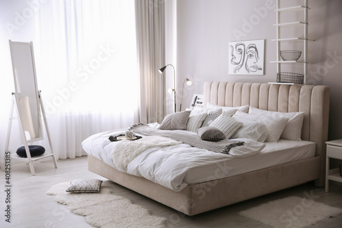 Cozy bedroom interior with beautiful picture and large mirror © New Africa