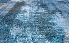 Close Up Of Gravel Strewn On An Icy Road.