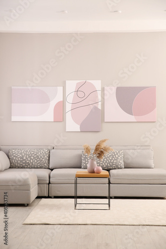 Stylish living room interior with big comfortable sofa and pictures © New Africa