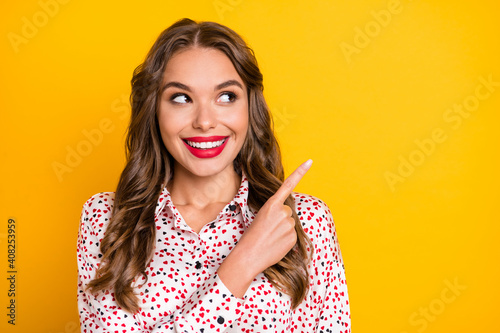 Portrait of adorable person look direct finger empty space beaming smile isolated on yellow color background © deagreez