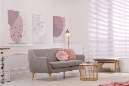 Obraz Stylish living room interior with comfortable sofa and beautiful pictures - fototapety do salonu