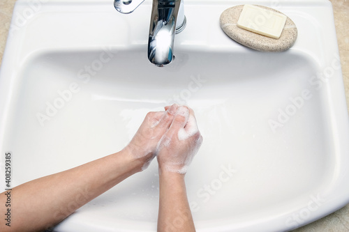 Fotografering A Hands with soap are washed under the tap with water