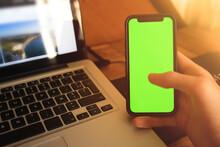 Homme Tenant Un Téléphone Portable Cellulaire Moderne (smartphone) Avec Un écran Vert Devant Un Ordinateur Portable