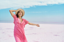 Freedom Woman In Pink Dress And Hat Carefree And Happy With Open Arms On Blue Sky White Salt Beach Landscape. Feeling Happiness Enjoying Her Travel Vacation.